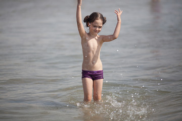 Little girl swims and plays in the sea