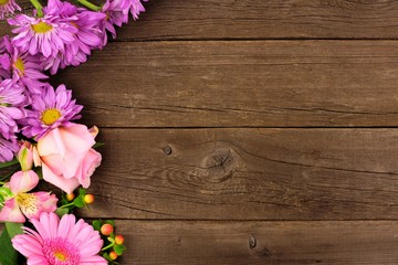 Side border of pink and purple flowers with rose, daisies and lilies against a rustic wood background. Copy space.