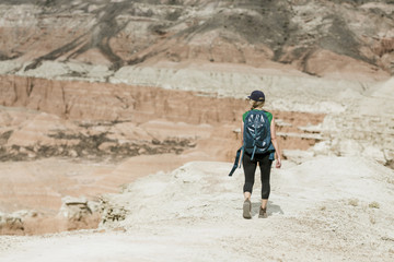 Rear view of female hiker with backpack walking at desert