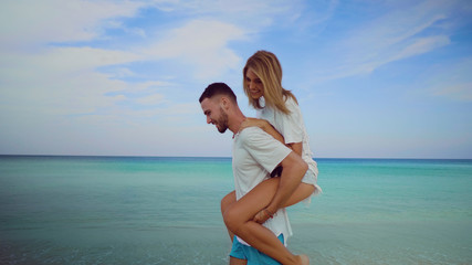 Beautiful happy couple having fun, doing piggyback on tropical sandy beach over sea and sky background