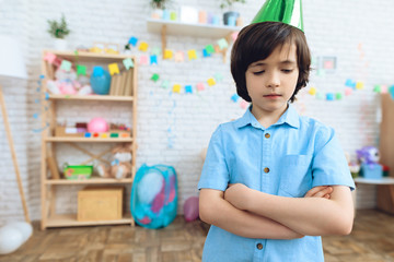 Little boy in festive hat is upset because no one has gone for his birthday.
