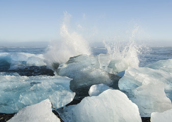 Scenic view of waves splashing on ice in sea against sky