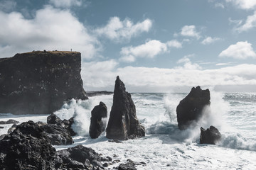 Scenic view of waves splashing on rock formations in sea against cloudy sky