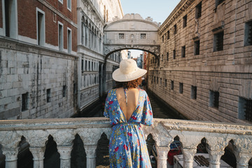 Rear view of woman wearing hat while standing by railing on bridge amidst buildings in city