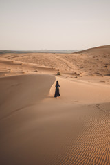 Rear view of woman walking at Sahara Desert against clear sky during sunset