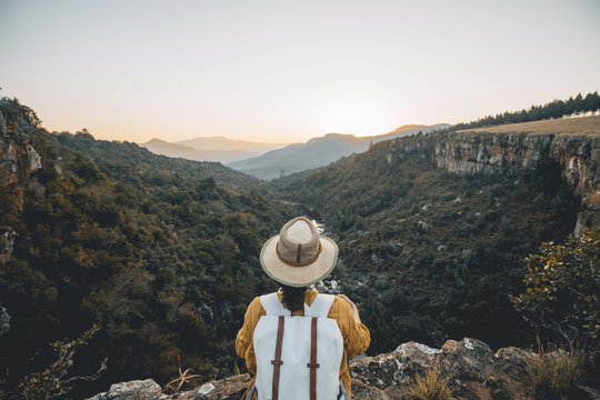 Rear view of woman with backpack looking at view while sitting on mountain against clear sky during sunset