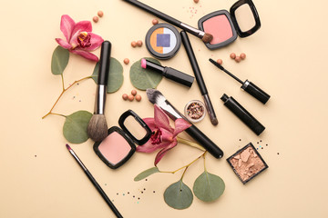 Decorative cosmetics and brushes of professional makeup artist on color background