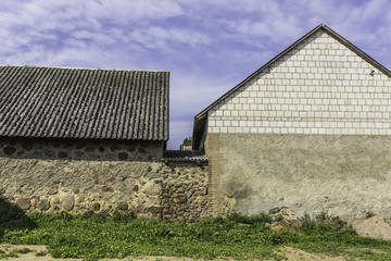 Slate roofs and stone walls of barns forming the agricultural farmyard . The end of the summer . Podlasie, Poland.