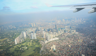 A view of the city of Manila through the window from the plane. Impressed photo of a tourist in flight over the capital. Philippines.