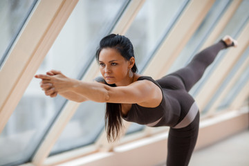 sport attractive woman brunette standing in Warrior three exercise, Virabhadrasana III pose on the mat in front of large windows.
