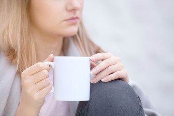 Close up portrait of woman drinking coffee in chilly morning