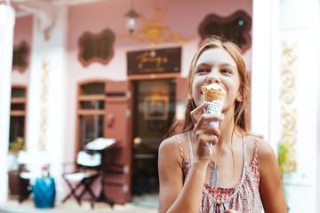 Child eating ice cream on the city street
