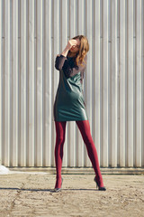 Girl in short leather dress and red tights posing outdoor