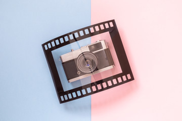 Flat lay of vintage camera and frame in form of analog film on multicolored background minimalistic concept.