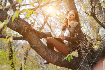 Hipster curly woman in brown jeans near tree in the park. Girl reading a book in a park outdoors. Study and recreation