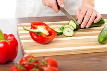 Chef woman cutting cucumber