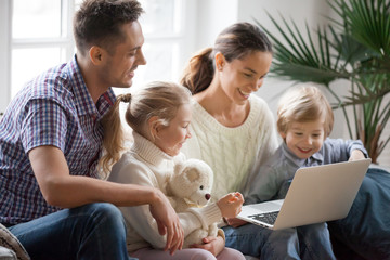 Young family with adopted children using laptop together at home, smiling parents and son daughter relaxing with computer looking at screen, married couple with kids shopping or watching video online