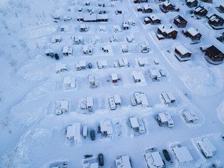 Aerial winter view of camping place with caravans, trailer park and cabin cottage houses, northern Sweden, near border with Norway