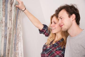 Einrichtung, Junges Paar überlegt eine Tapete an die Wand zu machen