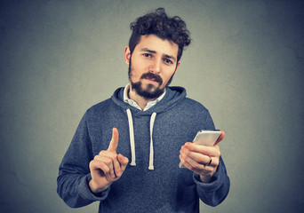 Man holding cell phone showing no, attention with finger hand gesture