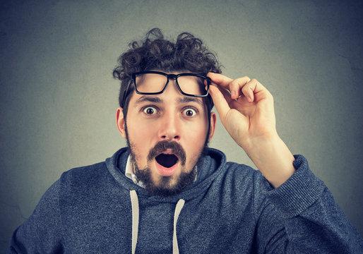 Shocked man taking off eyeglasses