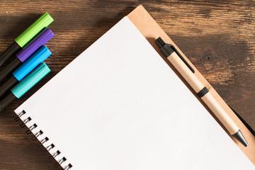 Cuaderno con bolígrafo y rotuladores