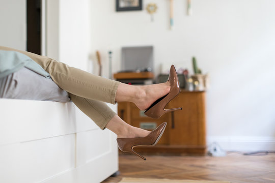 Tired woman resting with feet taking off brown high heeled shoes after work or walk at home, lying down on sofa/Foot fatigue, discomfort shoes concept