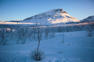 Beautiful cold mountain view of ski resort in Lapland, sunny winter day with slope, piste and ski lift