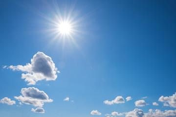 strahlend blauer Himmel mit Sonnenstern und Cumuluswolken