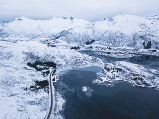 Aerial winter view of Lofoten Islands, Nordland, Norway, with fjord, road and mountains, shot from drone