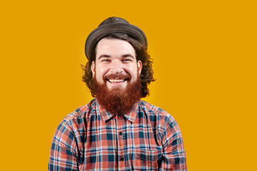 Happy smiling bearded hipster with hat looking confident at the camera over yellow background.