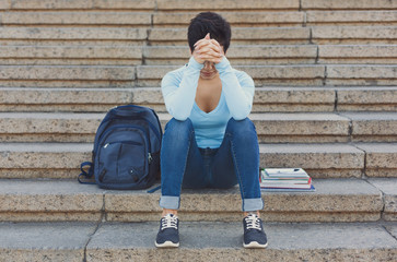 Tired shorthaired student girl sitting on the steps outdoors