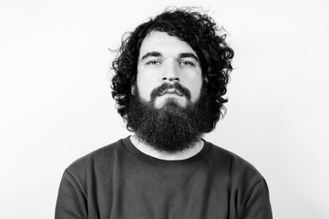Black and white portrait of hipster guy with curly hair looking at the camera. fashion bearded male model posing isolated over white background.