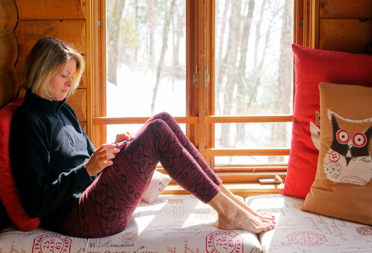 Pretty caucasian girl with a black hat watching her smartphone close to the window in a chalet for business and leisure.
