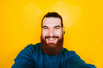 Smiling bearded hipster man taking selfie. Happy man with beard looking at camera on yellow background. Portrait of young hipster man.