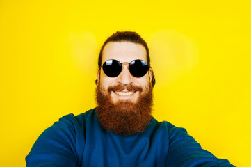 Portrait of young hipster man with beard in sunglasses taking a selfie. Smiling, happy man with beard.
