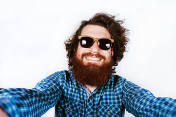 Cheerful happy bearded man with sunglasses looking at camera and taking selfie on white background in studio. Curly hair. Smiling young man with beard.