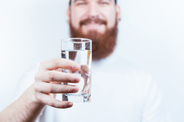 Happy man with beard holding a glass of water. Selective focus. Close up glass of water.