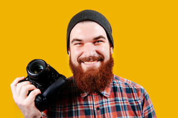 Handsome young man holding a DSLR Cheerful bearded hipster man with camera in hands smiling and looking confident at the camera. Photographer on yellow background.