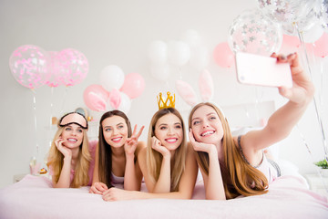Cheerful, joyful, charming, pretty, funny, dreamy, cute models lying on bed shooting self portrait on front camera, holding using smart phone, showing two fingers, peace symbol, enjoying theme party