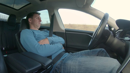 Business man sleeps on his drive home from work while his car is on autopilot.