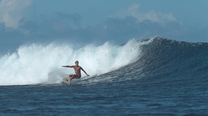 Extreme male surfboarder carves up a growing deep blue ocean swell on sunny day.