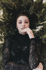 Overhead portrait of carefree young woman lying on plants at park