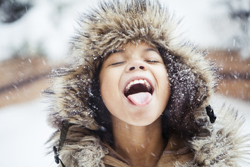 Playful girl with mouth open tasting snow during snowfall