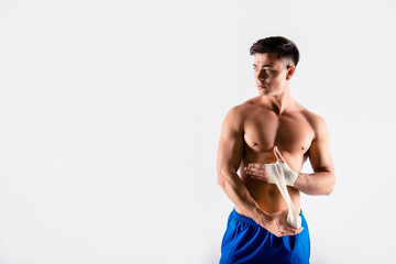 I'm in tune of winning. Portrait of sportive muscular naked, wearing blue shorts bodybuilder, he is using bandage to cover hands, preparation to competition isolated on white background, copy-space