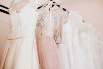 close-up embroidered with transparent beads top beige wedding dress which hangs on a hanger among other dresses