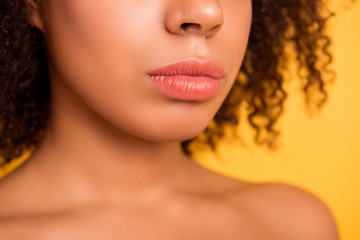 Cropped close up half-turned photo of big full natural tempting beautiful woman's lips with coral lipstick, isolated on yellow background