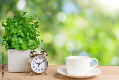 flower alarm clock and coffee cup morning background stock photo