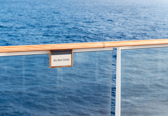 Do Not Climb warning sign on railing of cruise ship