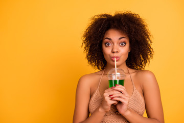 OMG! So delicious! Funny cute attractive careless mixed-race woman is drinking green alcohol cocktail is a plastic cup using a straw, isolated on bright vivid background, copy space